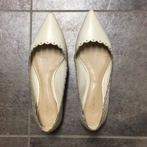 White leather Coach flats with gold stud detailing